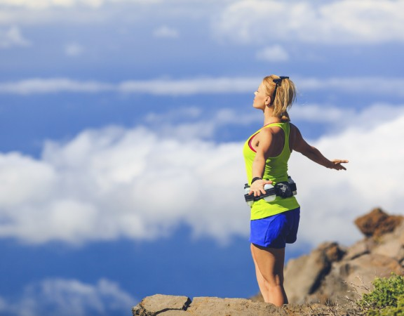 Happy woman runner joyful with arms raised outstretched smiling and ecstatic happiness with eyes closed. Fitness and exercise meditation in summer mountains nature outdoors, freedom concept.